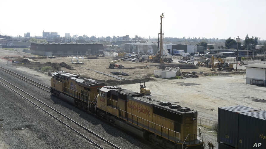 FILE - n this Friday, Feb. 26, 2016, photo a freight train passes one of the construction sites for the California High-Speed Rail Train, in Fresno, Calif. Sacramento County Superior Court Judge Michael Kenny ruled against plaintiffs in a lawsuit to