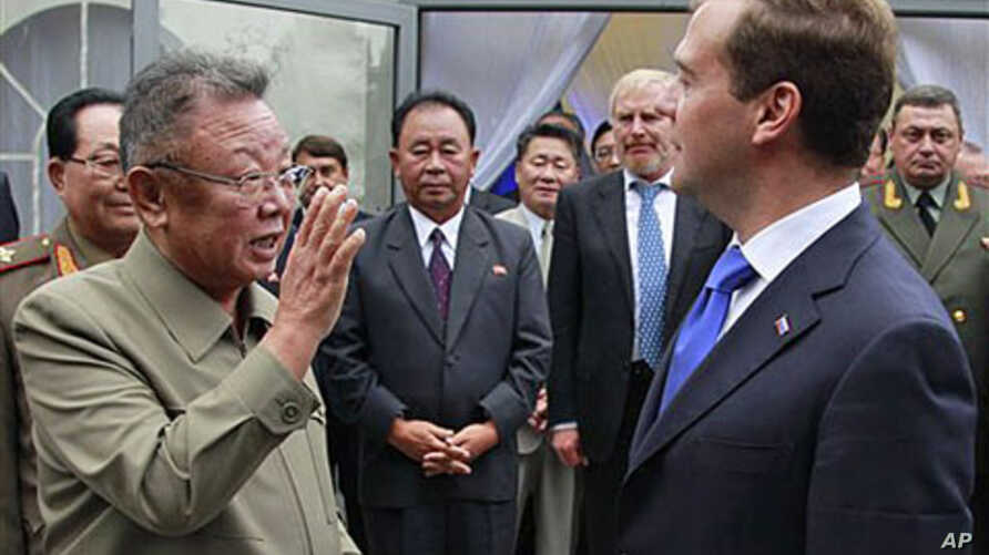 North Korean leader Kim Jong Il (L) says goodbye to Russian President Dmitry Medvedev (R) after a meeting at a military garrison, outside Ulan-Ude in Byryatia, Russia, August 24, 2011