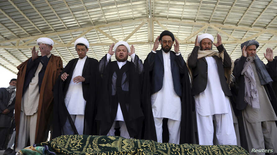 Afghan people offer funeral prayers behind the body of a civilian killed in Sunday's deadly suicide attack at a voter registration center, in Kabul, Afghanistan, April 23, 2018.