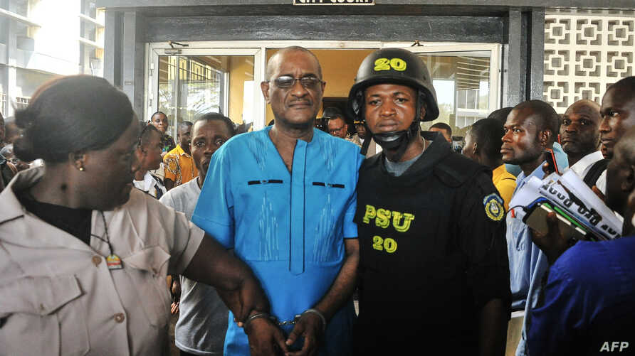 Former deputy governor of the Central Bank of Liberia Charles Sirleaf, center, the son of LIberia's former president Ellen Johnson Sirleaf, is escorted outside the City Court of Monrovia on March 4, 2019, where he was charged with economic sabotage.