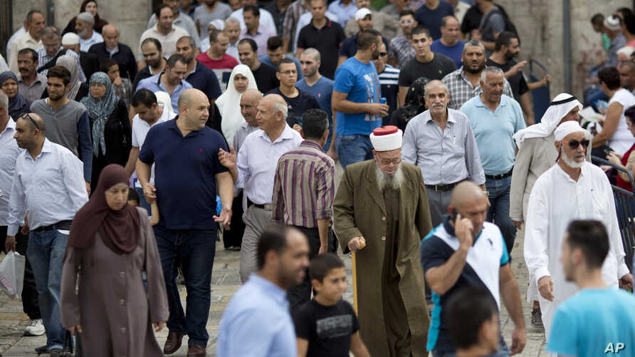 Palestinian Muslim worshipers walk back in Jerusalem's Old City after Friday prayers, Oct. 23, 2015.