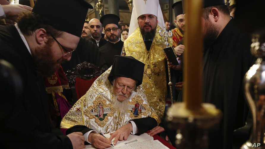"""Ecumenical Patriarch Bartholomew I, center, signs the """"Tomos"""" decree of autocephaly for the Ukrainian church as Metropolitan Epiphanius, center right, the head of the independent Ukrainian Orthodox Church looks on during the ceremony at the Patriarch"""