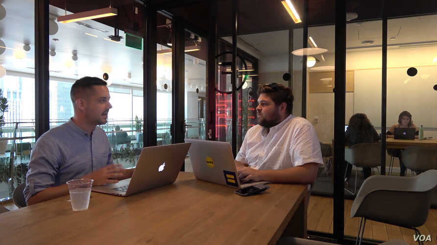 Brand strategist Phil Pallen (left) travels the world and works in the co-working spaces of a company called WeWork, seen here at a location in downtown Los Angeles. (Photo: M. O'Sullivan / VOA)