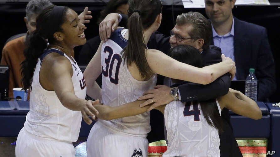 Connecticut head coach Geno Auriemma hugs Morgan Tuck (3) Moriah Jefferson (4) and Breanna Stewart (30) following the championship game against Syracuse at the women's Final Four in the NCAA college basketball tournament Tuesday, April 5, 2016.