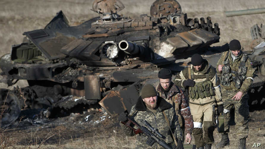 Russia-backed separatists walk after inspecting destroyed Ukrainian army tanks for  functional weapons and ammunition near the village of Lohvynove, outside Debaltseve, Ukraine, Sunday, Feb. 22, 2015, on the edge of the territory under their control....