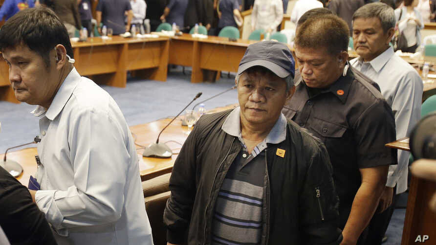 Former Filipino militiaman Edgar Matobato, center, walks under tight security after testifying at the Philippine Senate in Pasay, south of Manila, Philippines on Thursday, Sept. 15, 2016.