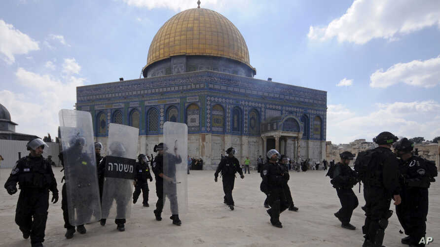 FILE - In this Friday, Oct. 5, 2012, photo, Israeli forces take position during clashes with Palestinian worshippers at the Al-Aqsa Mosque compound in Jerusalem's Old City.