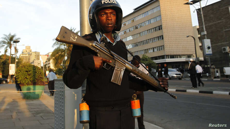 A riot policeman stands guard outside the main gate of the National Assembly in Kenya's capital Nairobi, Dec. 18, 2014.