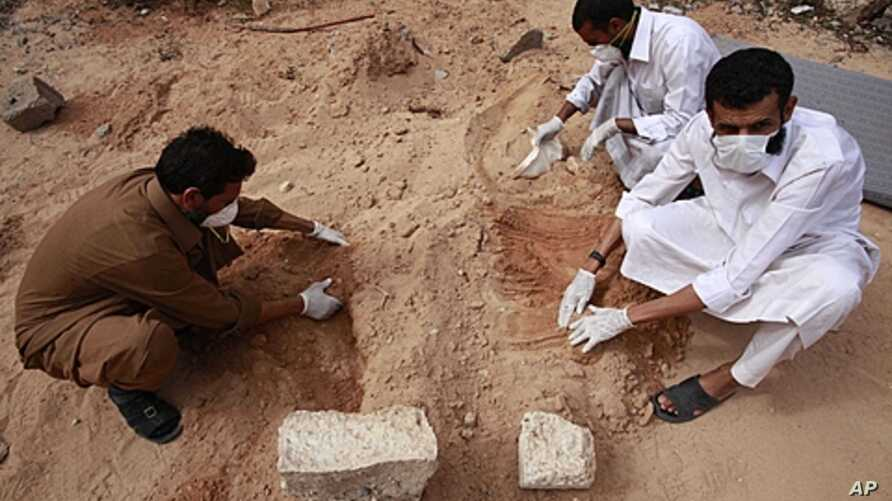 Volunteers dig up corpses in the city of Sirte, October 23, 2011.