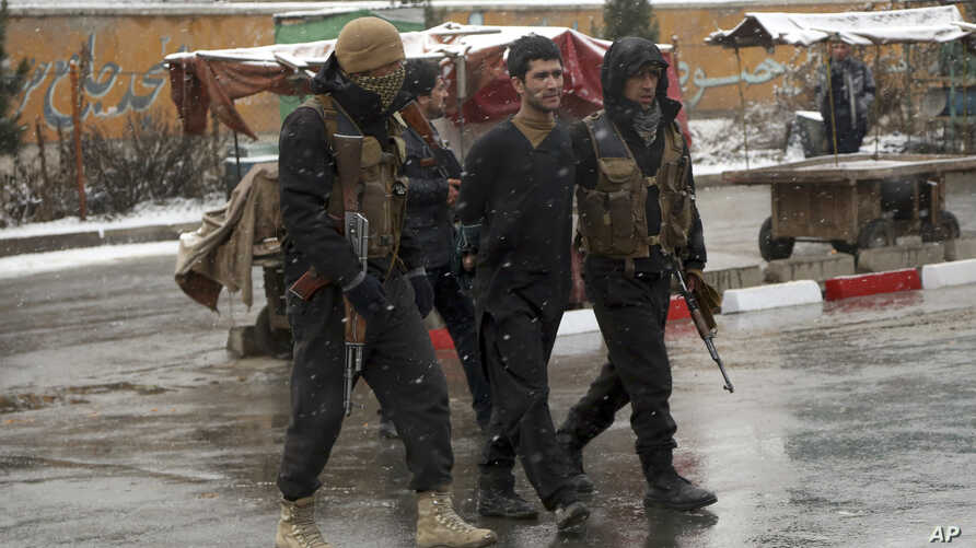 Afghan security personnel detain a suspect at the site of an attack on the Marshal Fahim military academy in Kabul, Afghanistan, Jan. 29, 2018.