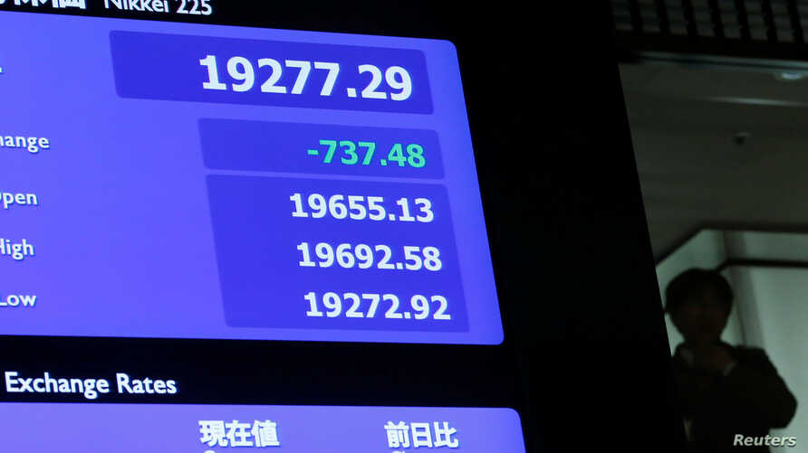 A man is seen behind an electronic board showing the Nikkei average after the New Year opening ceremony at the Tokyo Stock Exchange, held to wish for the success of Japan's stock market, in Tokyo, Jan. 4, 2019.