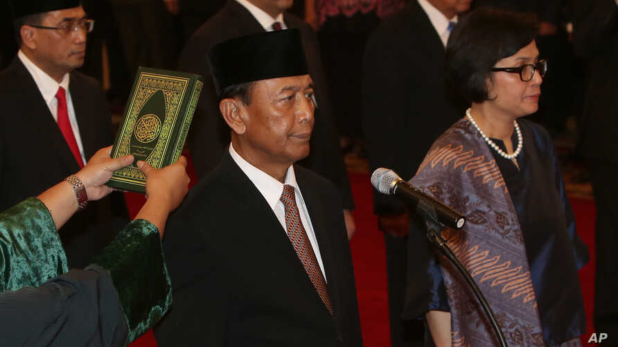 Indonesia's newly appointed Coordinating Minister for Legal, Politics and Security Affairs Wiranto, left, and Finance Minister Sri Mulyani Indrawati, right, are sworn in during the inauguration ceremony for the new cabinet members at the State Palace