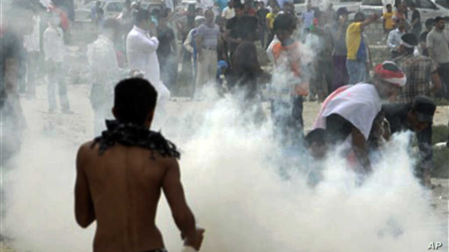 Anti-government protesters react to tear gas fired by riot police along a main highway in Manama, Bahrain, March 13, 2011