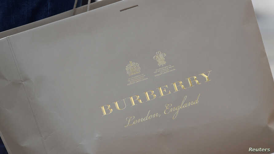 FILE - A shopper carries a Burberry bag in central London, Britain.