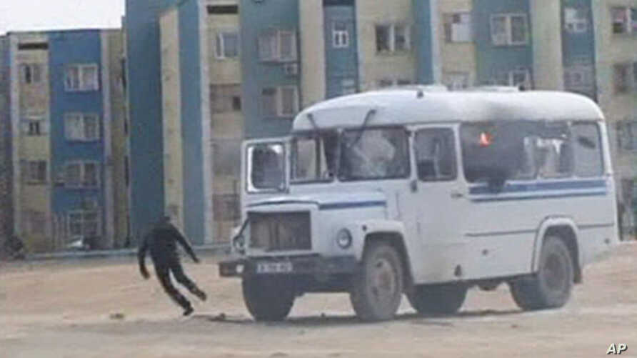 A protester runs from a police vehicle in the Kazakh town of Zhanaozen in this still image taken from video acquired by Reuters TV, December 16, 2011.