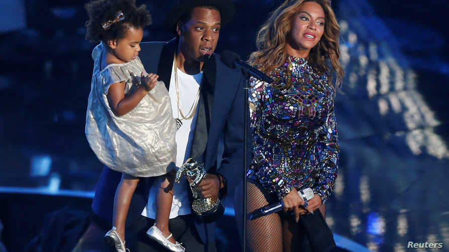 FILE - Jay-Z presents the Video Vanguard Award to his wife, Beyonce, as he holds their daughter, Blue Ivy, during the 2014 MTV Video Music Awards in Inglewood, California, Aug. 24, 2014.