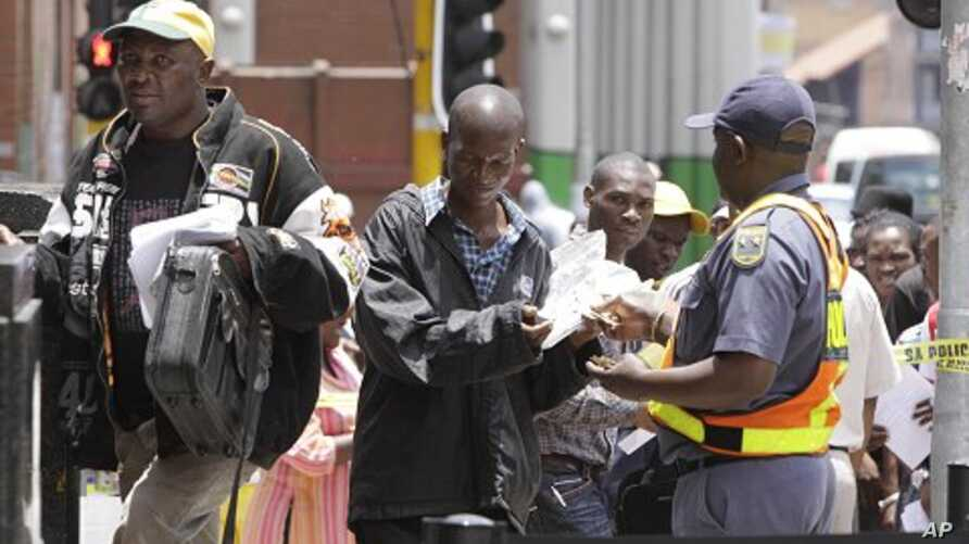 Zimbabweans pass a police cordon to submit their application forms outside the Immigration offices in Johannesburg, in a last minute bid to have their status in South Africa legalized (File Photo)