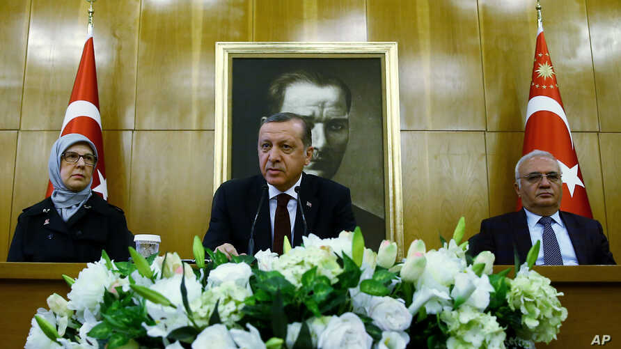 Turkish President Recep Tayyip Erdogan, center, flanked by Family Affairs Minister Sema Ramazanoglu, left, and Economy Minister Mustafa Elitas, speaks to the media at the Ataturk Airport in Istanbul, March 29, 2016.