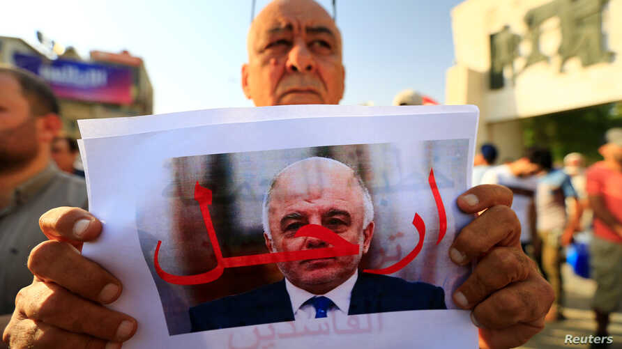 """A protester holds a picture of Iraqi Prime Minister Haider al-Abadi with """"Step Down"""" written on it during a protest at Tahrir square in Baghdad, Iraq, July 27, 2018."""