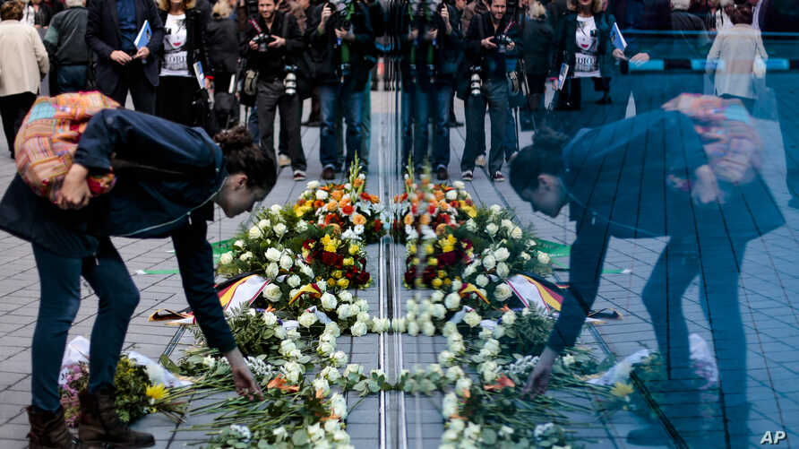 A woman lays flowers at the new monument for the victims of euthanasia in Berlin, Sept. 2, 2014.