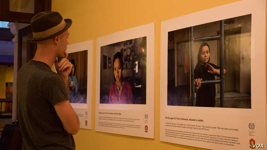 "Audiences look at photos in the exhibition ""No one should work this way"" in Phnom Penh."