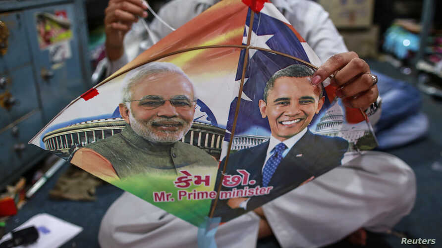 An employee ties threads on a kite, with portraits of Indian Prime Minister Narendra Modi (L) and U.S. President Barack Obama, ahead of Obama's visit, in Mumbai, Jan. 23, 2015.