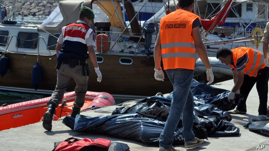 A Turkish paramilitary officer and local workers collect the bodies of migrants after coast guard officials said 13 migrants  died after their boat collided with a ferry off the Turkish coast near Ayvacik, Canakkale, Turkey, Sept. 20, 2015.