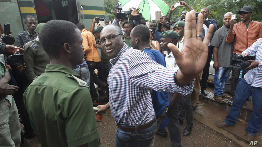 FILE - Evans Mawarire waves goodbye as he is taken into a prison truck at the magistrates courts in Harare.