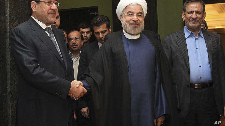 FILE - Iran's President Hassan Rouhani (c) shakes hands with Iraqi Prime Minister Nouri al-Maliki, in their meeting in Tehran, Iran.