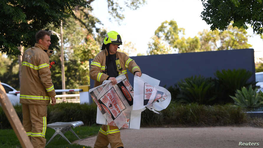 A fire fighter is seen carrying hazardous material bags into the South Korean consulate in Melbourne, Australia, January 9, 2019.