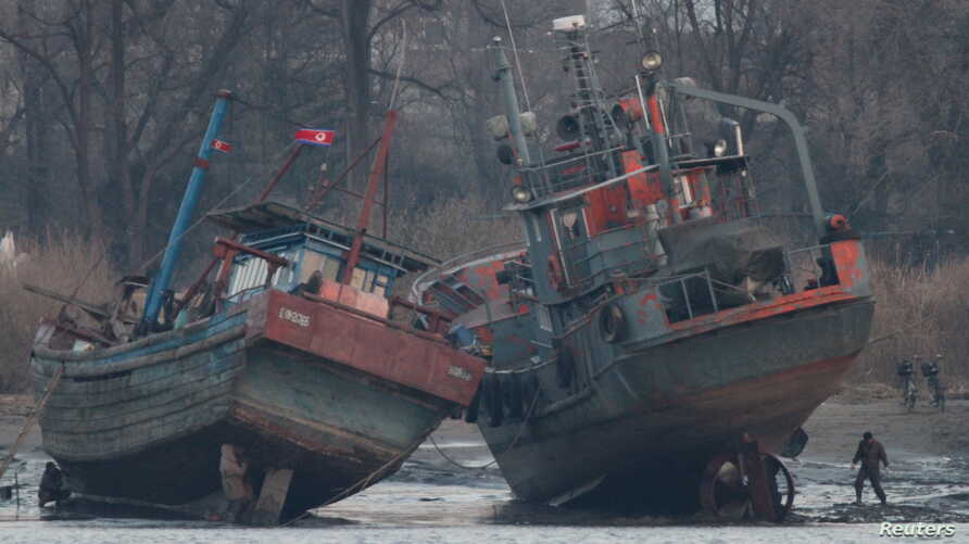 A cargo boat (R) is seen on the bank of the Yalu River in Sinuiju, opposite the Chinese border city of Dandong, March 14, 2016.