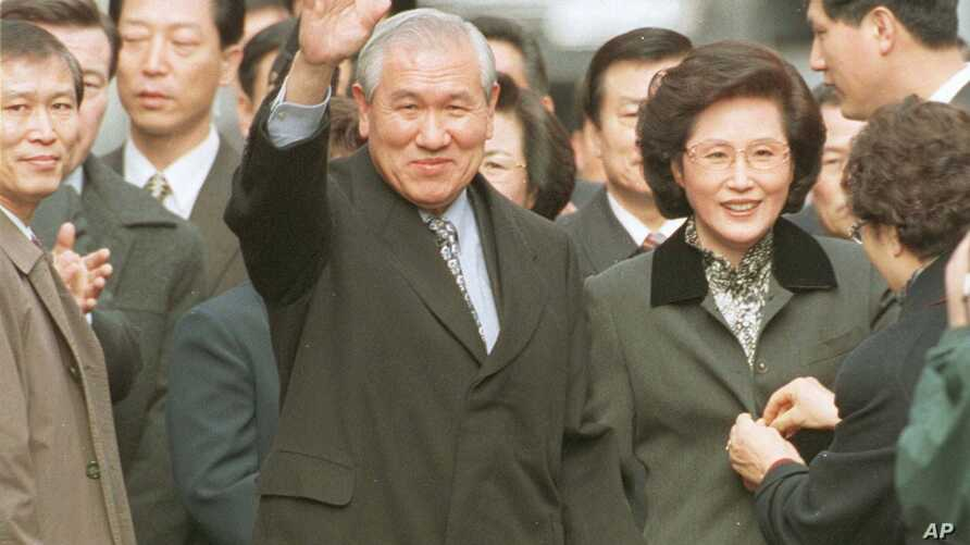 A smiling former South Korean President Roh Tae-woo, with his wife Kim Ok-sook standing beside him, waves to his supporters and neighbors upon arrivial at his home after he was released from the Seoul prison in a vspecial amnesty, Dec. 22, 1997.