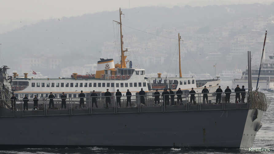 U.S. sailors stand aboard the USS Ross as leaves from the port in Istanbul, Nov. 13, 2014.
