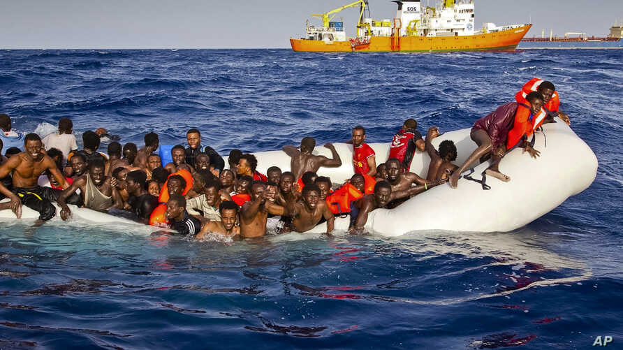 Migrants ask for help from a dinghy boat as they are approached by the SOS Meditrranee's ship Aquarius, background, off the coast of the Italian island of Lampedusa, April 17, 2016.
