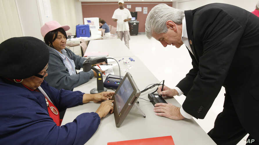 Poll workers Bertha Moses, left, and Florine Williams, check Mississippi Gov. Phil Bryant's driver's license as part of the voter ID procedure for anyone who casts a ballot, in a Jackson, Mississippi, precinct, Nov. 3, 2015.