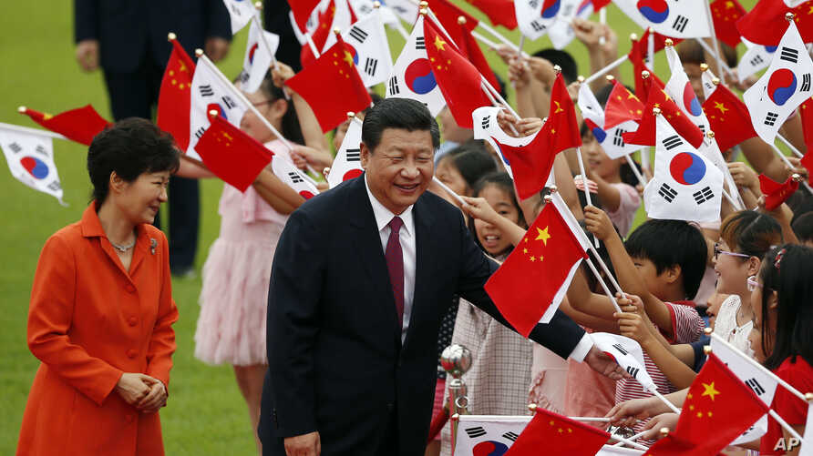 Chinese President Xi Jinping, right, and his South Korean counterpart Park Geun-hye, left, greet children during a welcome ceremony at the Presidential Blue House in Seoul, South Korea,  July 3, 2014.