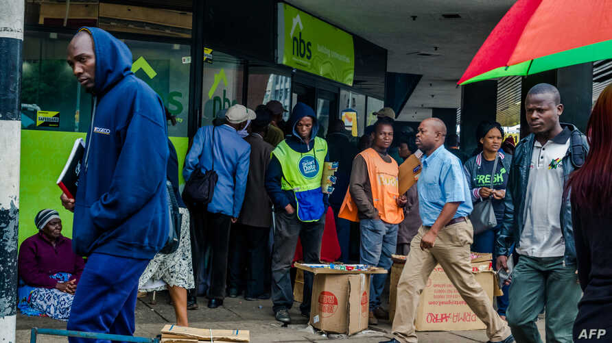 Residents walk in a street as others queue outside a bank in Harare, Nov. 15, 2017.
