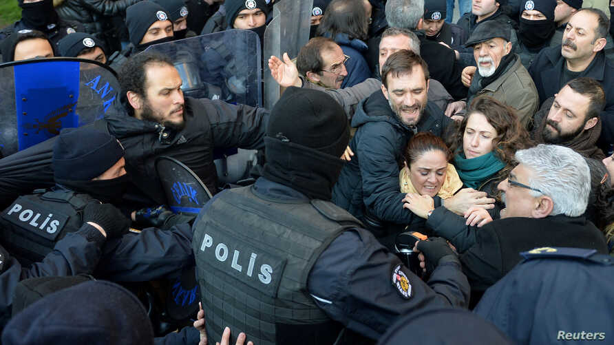 Demonstrators scuffle with riot police during a protest against the detention of the head of the Turkish Medical Association and other leaders of the doctors' union, in Ankara, Turkey, Jan. 30, 2018.