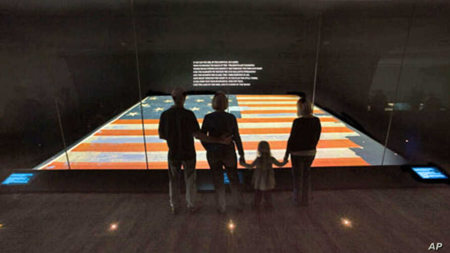Visitors view the Star-Spangled Banner at the National Museum of American History.