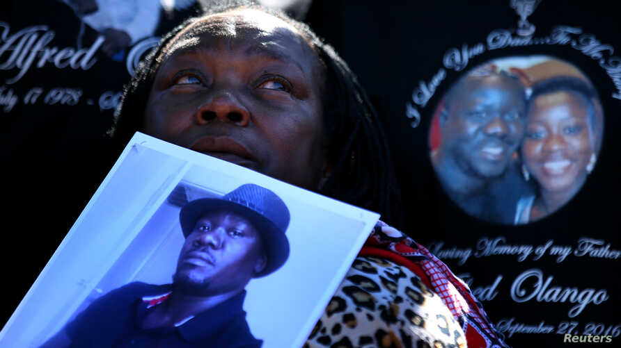FILE - A woman holds a picture of Alfred Olango as she listens to speeches during a rally and march to protest the fatal police shooting of the Ugandan immigrant in El Cajon, California, Oct. 1, 2016.