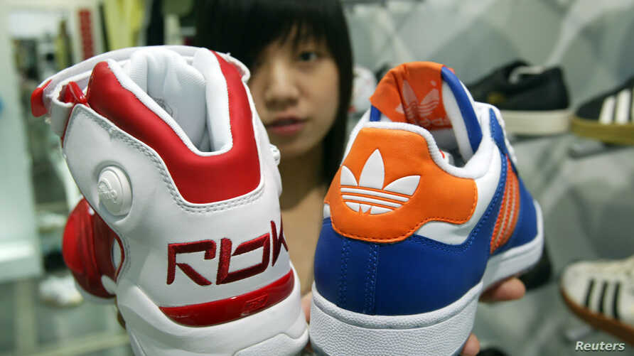 A saleswoman holds up athletic shoes by Reebok and Adidas in Taipei August 4, 2005.