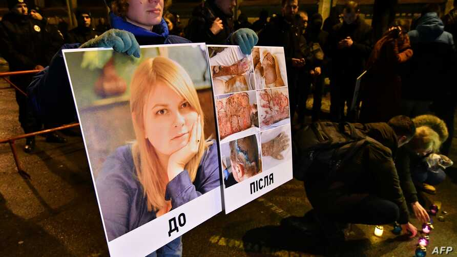 In this Feb. 4, 2019 photo, an activist holds a portrait of Kateryna Gandzyuk along with photos showing her traumas after the July 2018  acid attack that eventually killed the Ukrainian anti-corruption campaigner.