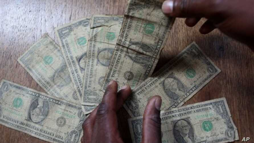 In this Friday, July 2, 2010 picture an unidentified man shows dirty one dollar notes before washing them in Harare, Zimbabwe. The washing machine cycle takes about 45 minutes _ and George Washington comes out much cleaner than before in Zimbabwe-sty