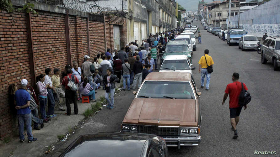 People line up outside a supermarket next to motorists queuing for gas near a gas station of the Venezuelan state-owned oil company PDVSA in San Cristobal, Venezuela November 10, 2018.