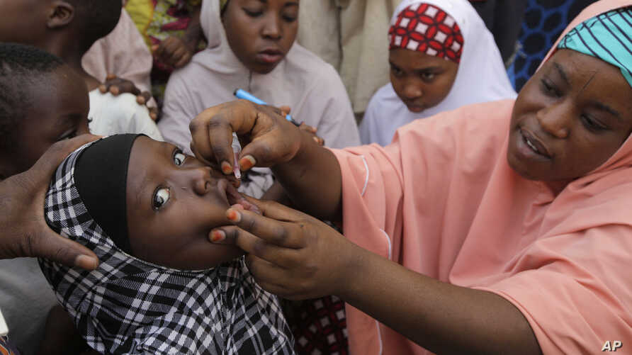 FILE -  Health official administers a polio vaccine to a child in Kawo Kano, Nigeria.
