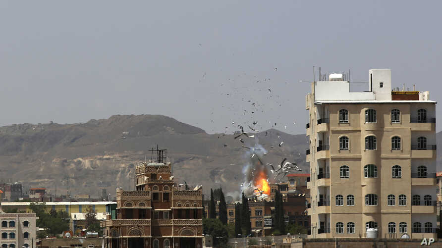 Debris and smoke rise after a Saudi-led airstrike hits an army base in Sanaa, Yemen, Sept. 14, 2015.