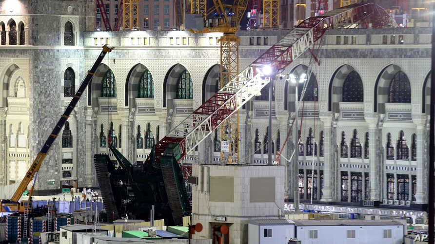 A towering construction crane, center, is seen collapsed over the Grand Mosque, in Mecca, Saudi Arabia, early Saturday morning, Sept. 12, 2015.