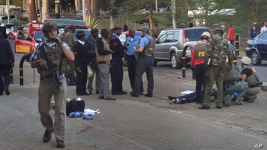 Kenya Embassy Attack: Unidentified U.S. Embassy personnel and Kenyan security forces stand near to the body, right, of a man who was killed outside the U.S. Embassy in Nairobi, Kenya Thursday, Oct. 27, 2016.
