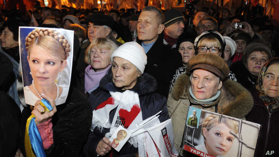 Supporters of the Ukrainian Opposition party hold up photos of the imprisoned former Ukrainian PM, Yulia Tymoshenko, whilst taking part in a rally outside the Central Elections Commission building in Kiev, Ukraine, November 12, 2012.