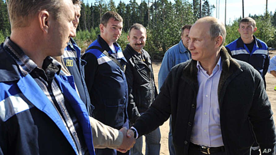 Russian Prime Minister Vladimir Putin, right, meets with employees of the Portovaya gas compressor station outside Vyborg, some 170 km northwest from St. Petersburg, Russia, Sept. 6, 2011.